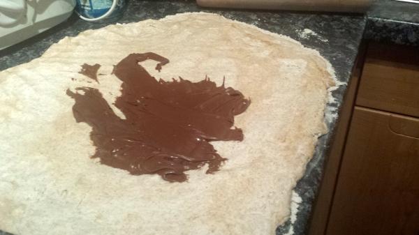 Nutella wird auf die Oberfläche des Teigs gestrichen.